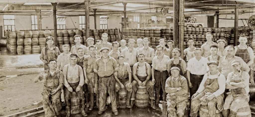 Old black and white photo of men in beer warehouse