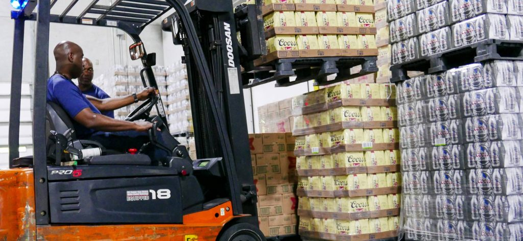 Man driving forklift carrying Coors beer