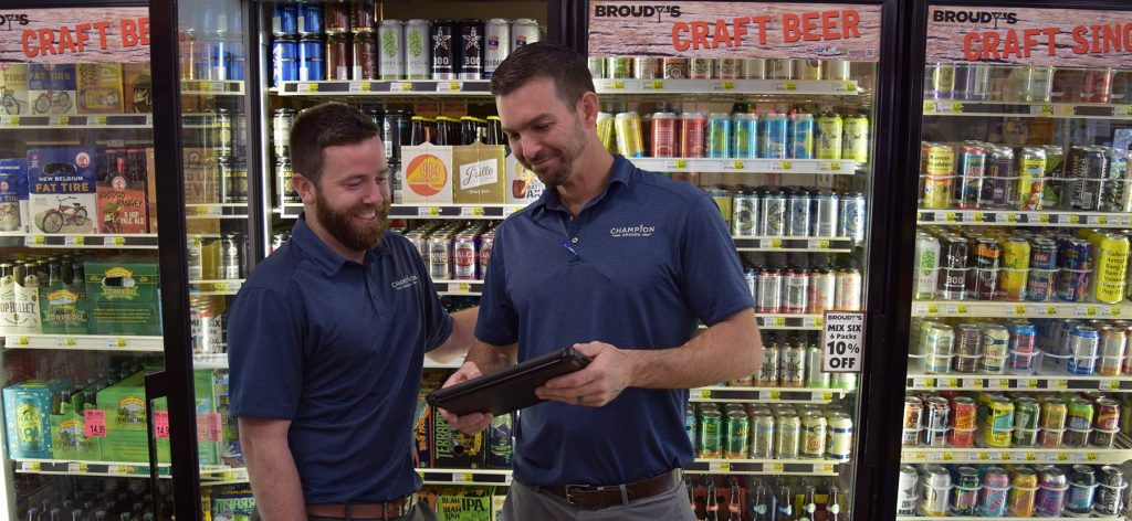 Two men in Champion Brands shirts looking at an ipad inside standing next to beer in a convenience store